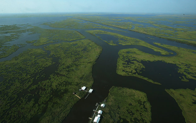 PLAQUEMINES PARISH, LA - AUGUST 25: Structures stand along deterioring wetlands on August 25, 2015 in Plaquemines Parish, Louisiana. Louisiana is currently losing its wetlands at a rate of one football field per hour. Wetlands act as a storm buffer and their diminished size was a major contributing factor to the force with which Hurricane Katrina's storm surge hit New Orleans. The state is implementing efforts to restore the wetlands. The tenth anniversary of Hurricane Katrina is August 29. (Photo by Mario Tama/Getty Images)