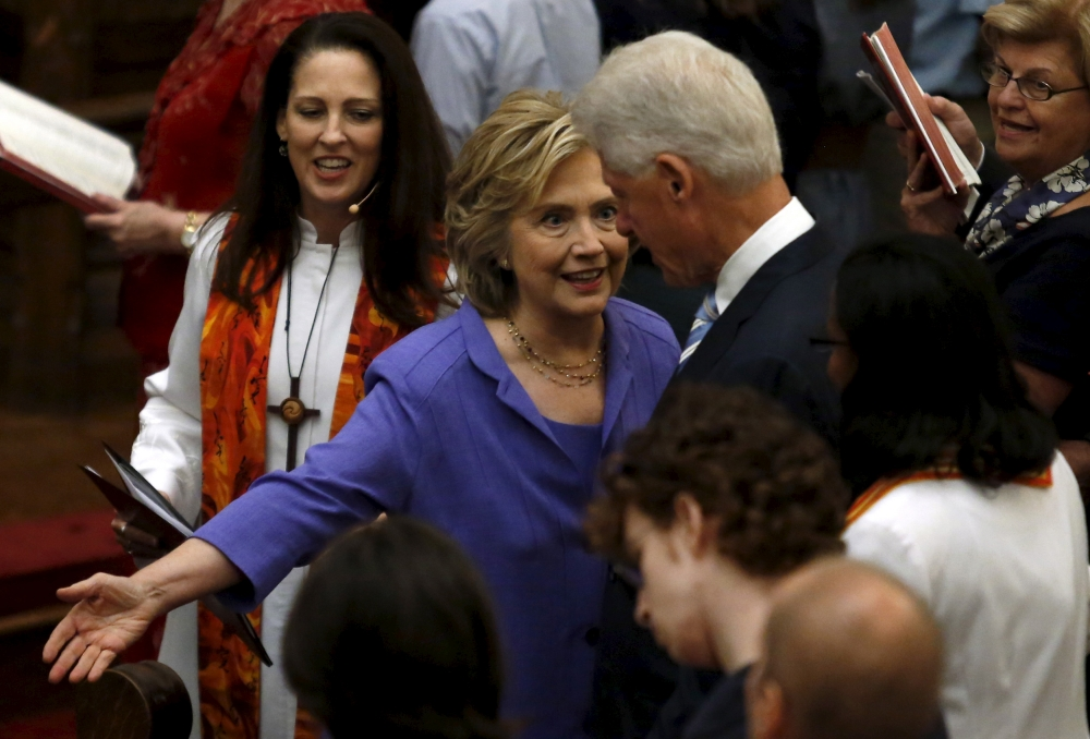 U.S. Democratic presidential candidate Hillary Clinton gestures to former U.S. President Bill Clinton to take a seat first at the Foundry United Methodist Church's bicentennial service in Washington, September 13, 2015.