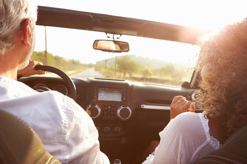 Mature-Couple-Driving-Along-Country-Road-In-Open-Top-Car