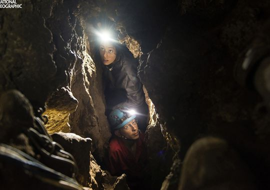 Lee Berger's daughter, Megan, and underground exploration team member Rick Hunter navigate the narrow chutes leading to the Dinaledi Chamber of the Rising Star cave in South Africa where fossil elements belonging to H. naledi, a new species of human relative, were discovered. The find was announced by the University of the Witwatersrand, the National Geographic Society and the South African National Research Foundation and published in the journal eLife. (Photo: Robert Clark, National Geographic)