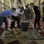 Palestinians gather stones that were stored in the Al Aqsa mosque beforehand, as they clean up after clashes with Israeli police on the compound known to Muslims as Noble Sanctuary and to Jews as Temple Mount in Jerusalem's Old City September 13, 2015. Israeli police raided the plaza outside Jerusalem's al-Aqsa mosque on Sunday in what they said was a bid to head off Palestinian attempts to disrupt visits by Jews and foreign tourists on the eve of the Jewish New Year. REUTERS/Ammar Awad