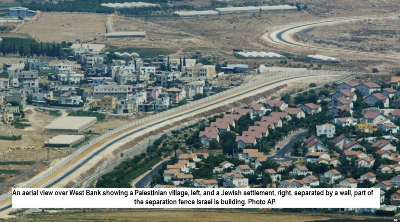An aerial view over West Bank showing a Palestinian village, left, and a Jewish settlement, right, separated by a wall, part of the separation fence Israel is building.